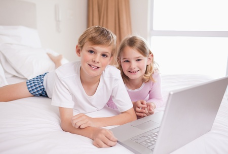 Siblings using a laptop in a bedroom Stock Photo - 11686337