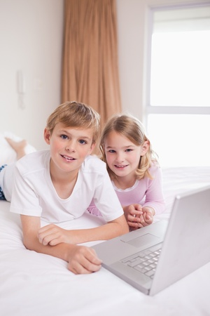 Portrait of children using a laptop in a bedroom photo