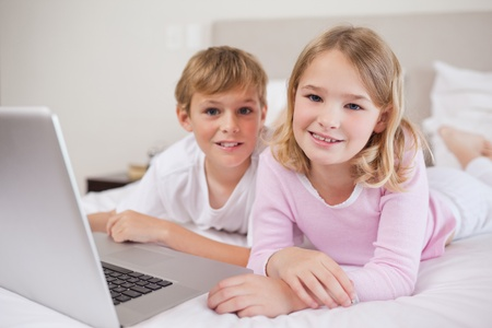 Cute children using a notebook in a bedroom photo