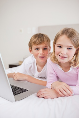 Portrait of cute children using a laptop in a bedroom photo