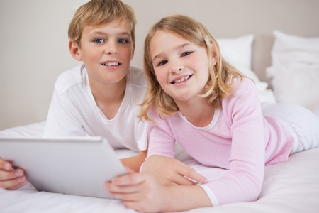 Children using a tablet computer in a bedroom photo