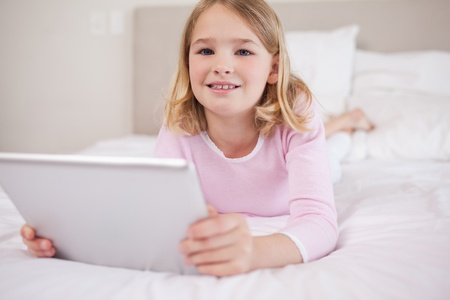 Girl using a tablet computer in a bedroom photo