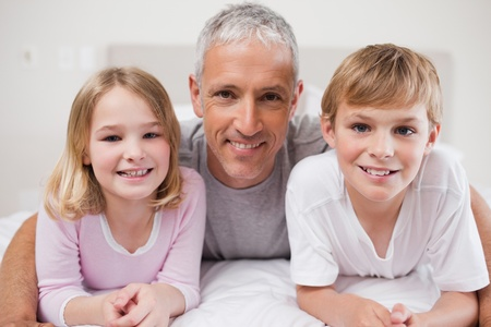 Smiling siblings and their father posing in a bedroom Stock Photo - 11683179
