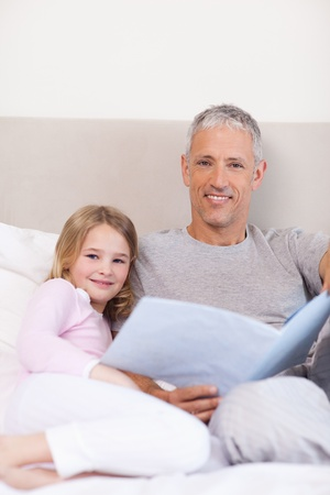 Portrait of a father reading a story to his daughter in a bedroom photo