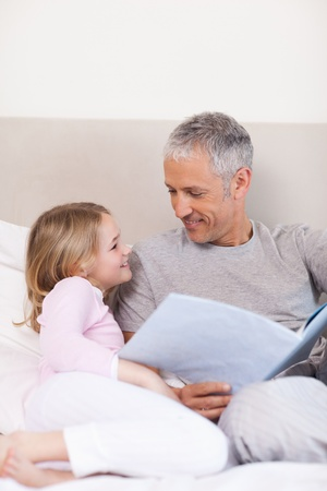 Portrait of a smiling father reading a story to his daughter in a bedroom Stock Photo - 11685481