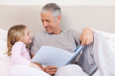 Happy father reading a story to his daughter in a bedroom photo