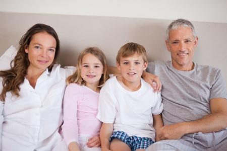 pijama: Familia feliz acostado en una cama mientras se mira a la c�mara Foto de archivo