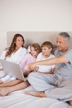 Portrait of a family using a notebook in a bedroom Stock Photo - 11684018