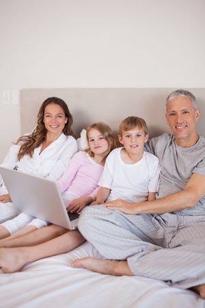 Portrait of a family using a laptop in a bedroom Stock Photo - 11684831