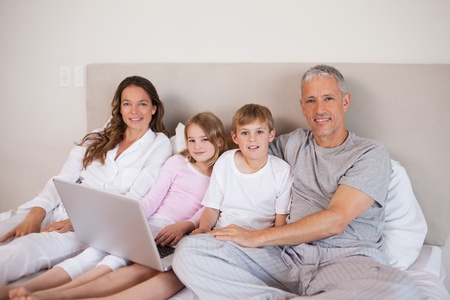 Smiling family using a laptop in a bedroom Stock Photo - 11683896