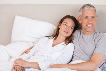 Happy couple lying on a bed looking away from the camera Stock Photo - 11684638
