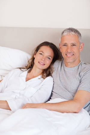Portrait of a couple lying on a bed while looking at the camera Stock Photo - 11685717