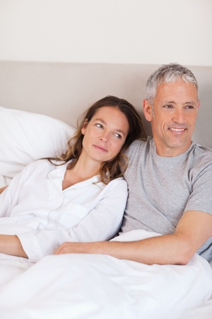 Portrait of a happy couple lying on a bed while looking away from the camera Stock Photo - 11685644