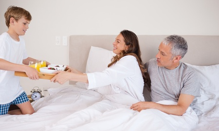 Boy serving breakfast to his parents in their bedroom Stock Photo - 11686076