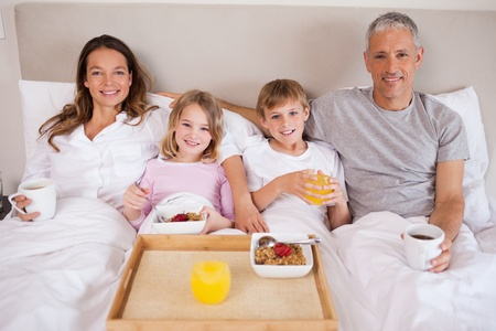 Family having breakfast in a bedroom while looking at the camera photo