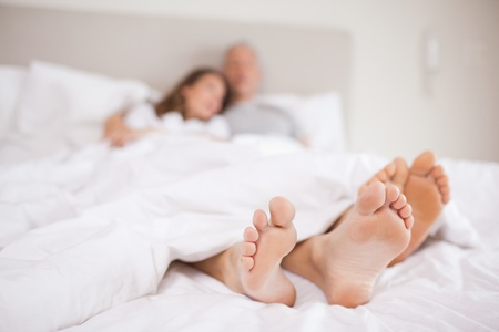 Lovely couple lying in a bed with the camera focus on their feed photo