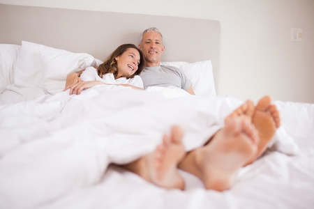 Charming couple lying in a bed while hugging photo