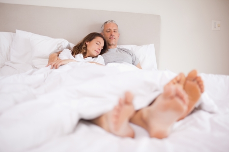 Couple sleeping in their bedroom with their eyes closed photo