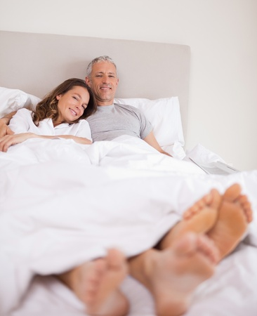 Portrait of a lovely couple lying on their bed while looking at the camera photo