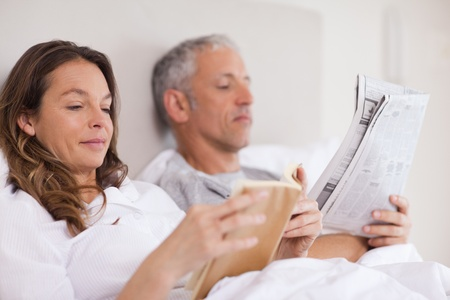 Woman reading a book while her husband is reading the news in their bedroom Stock Photo - 11685092