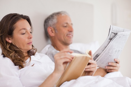 Woman reading a book while her husband is reading a newspaper in their bedroom photo