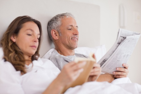 Happy woman reading a book while her husband is reading a newspaper in their bedroom photo