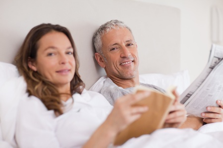 Happy woman reading a book while her husband is reading the news in their bedroom photo