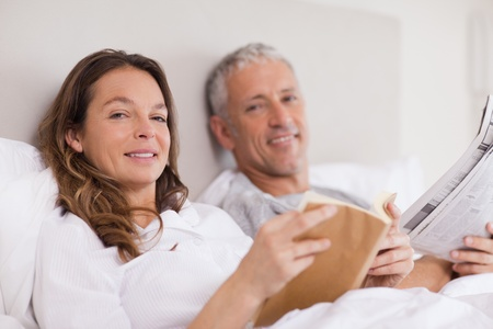 Smiling woman reading a book while her husband is reading the news in their bedroom Stock Photo - 11685081
