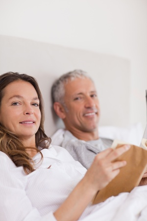 Portrait of a woman reading a book while her husband is reading the news in their bedroom Stock Photo - 11685687