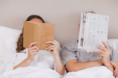 Woman reading a book while her companion is reading a newspaper in their bedroom photo