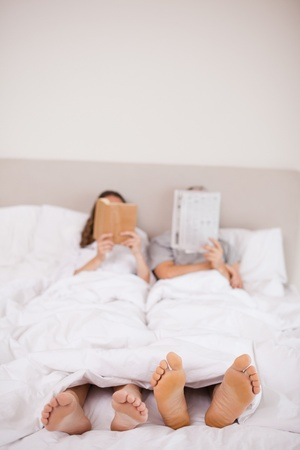 Portrait of woman reading a book while her companion is reading a newspaper in their bedroom photo
