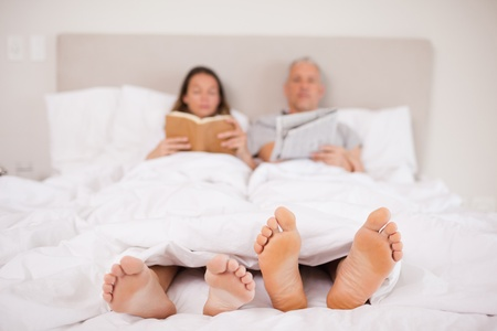 Woman reading a book while her companion is reading the news in their bedroom Stock Photo - 11686395
