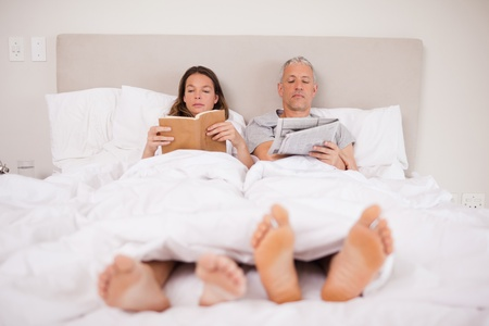 Man reading the news while his wife is reading a book in their bedroom photo