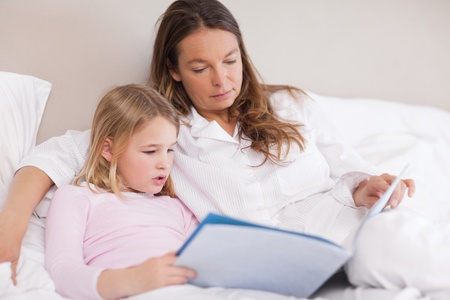 Cute girl reading a book with her mother in a bedroom photo