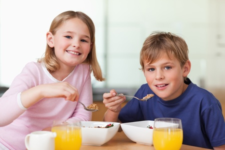 cereal bowl: Children having breakfast in a kitchen