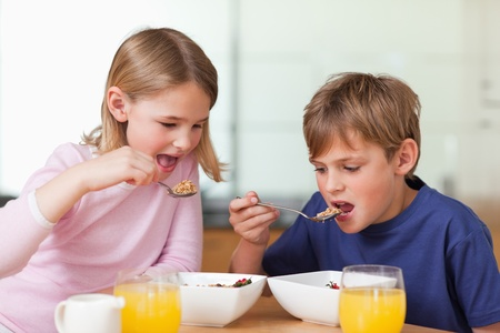 Young children having breakfast in a kitchen photo