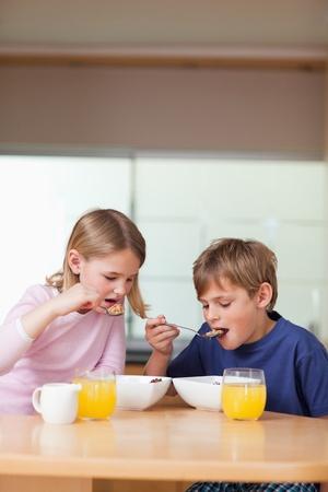 Portrait of children having breakfast in a kitchen photo