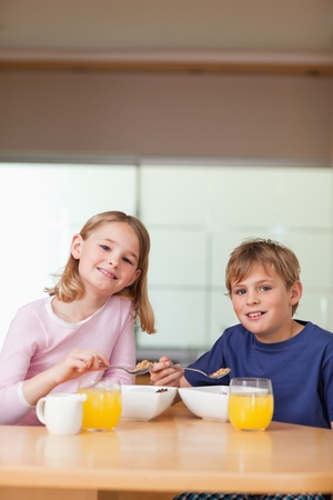 Portrait of young children having breakfast in a kitchen photo