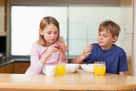 little table: Cute children eating strawberries for breakfast in a kitchen