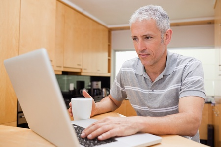 Man using a laptop while drinking coffee in a kitchen photo