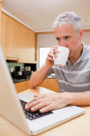 Portrait of a man using a laptop while drinking coffee in a kitchen photo