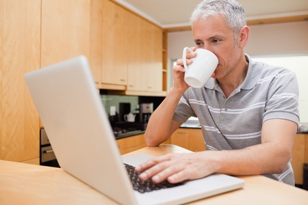 Happy man using a notebook while drinking coffee in a kitchen photo