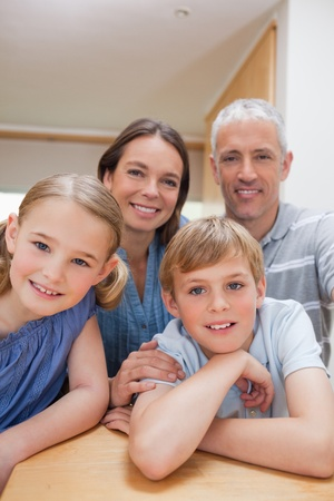 Portrait of a cute family posing in a kitchen while looking at the camera photo