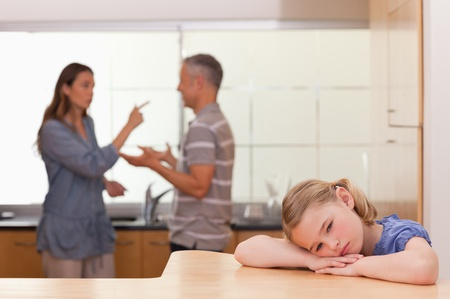 Sad little girl listening her parents having an argument in a kitchen photo