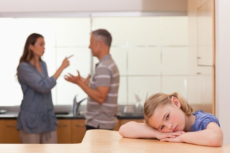 Sad little girl listening her parents having an argument in a kitchen Stock Photo - 11686484