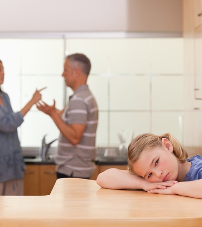 argues: Portrait of a sad girl listening her parents arguing in a kitchen Stock Photo