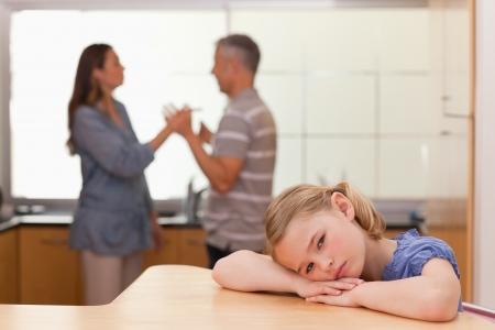 violencia: Muchacha triste escuchar a sus padres discutiendo en una cocina