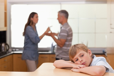 Sad little boy hearing his parents arguing in a kitchen photo