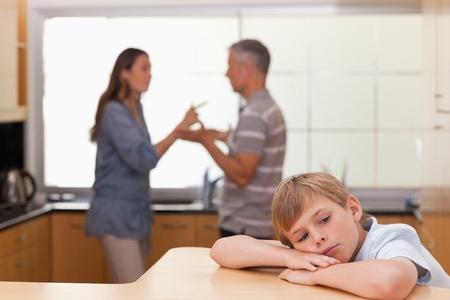 alcoolisme: Triste petit gar�on entendant ses parents se disputer dans une cuisine