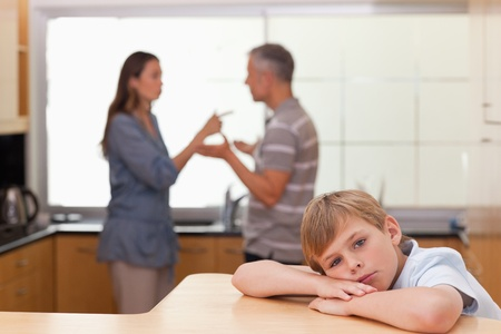Sad little boy hearing his parents arguing in a kitchen Stock Photo - 11684922